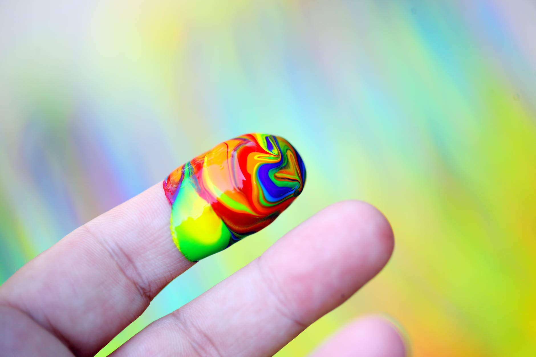 person showing multi coloured paint on his index finger